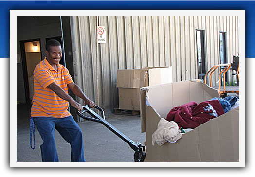 smiling man moving big box of clothes